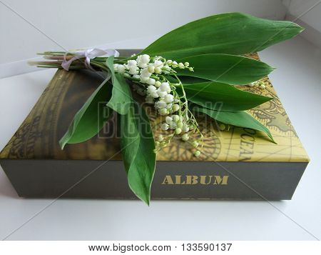 a bouquet of lilies of the valley alily of the valley bouquet and a photo album on a white backgroundnd the album