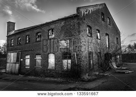 Picture of an old abandoned building sitting in a desolate countryside
