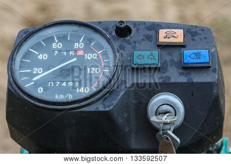 Closeup of dirty old motorcycle speedometer with drops from rain during using motorcycle on the off road with ignition key