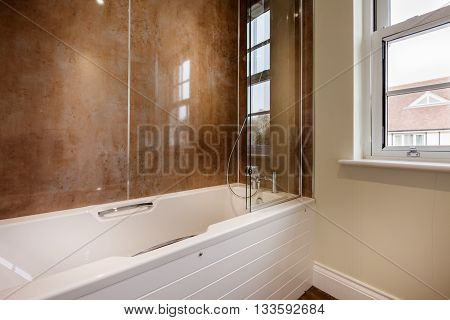 Bathroom with white coloured bathroom and shower attachment