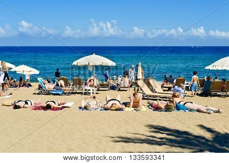 BARCELONA, SPAIN - MAY 30: People sunbathing at La Barceloneta Beach on May 30, 2016 in Barcelona, Spain. This popular beach hosts about 500,000 visitors from everywhere during the summer season