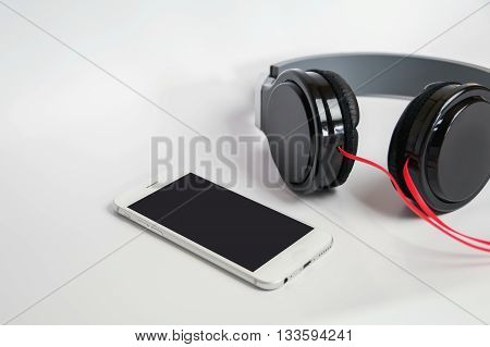 music concept - smartphone and headphones isolated on white background,smartphone and headphones close-up