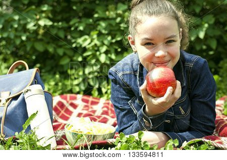 Girl with apple and crisps lies on a plaid on the grass