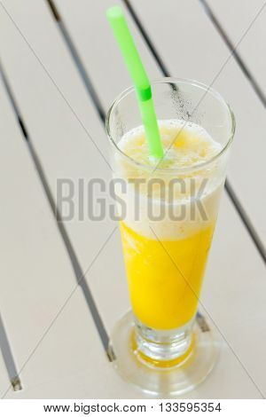 orange smoothies in glass and green tube on wood table