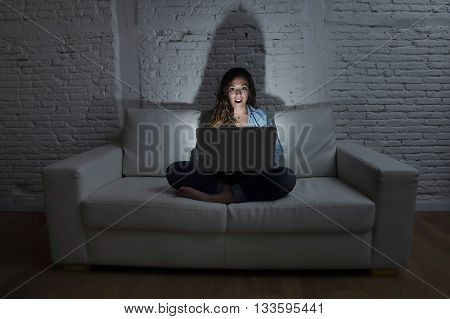 young attractive woman at home sitting at living room sofa couch using laptop computer in dark evening light with intense face expression in internet and network addiction concept at night
