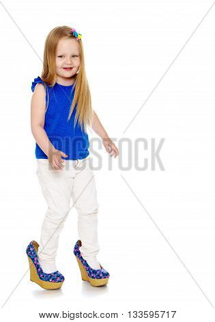 Happy little girl with long blond hair, put on the legs of mom's shoes that she doesn't come in my size-Isolated on white background