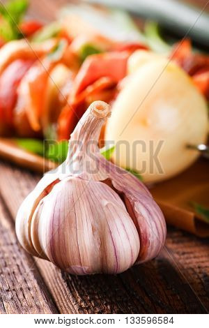 Single Garlic Bud With Violet Skin In Front Of Few Skewers