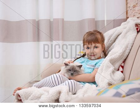 Little girl and cat sitting on the sofa in living room