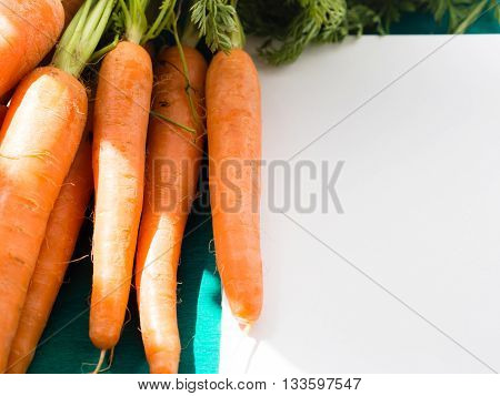 Dark Green Background With Carrots And Open Note Book