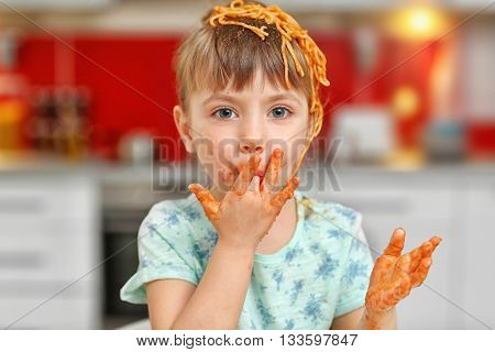 Adorable little girl eating spaghetti in kitchen