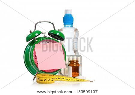 Medical concept - green alarm clock with pills, water and measuring tape,  isolated on white background