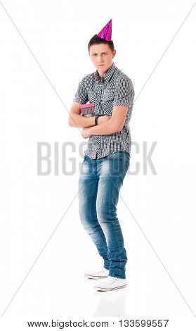 Unhappy young man with birthday hat standing full length isolated on white background