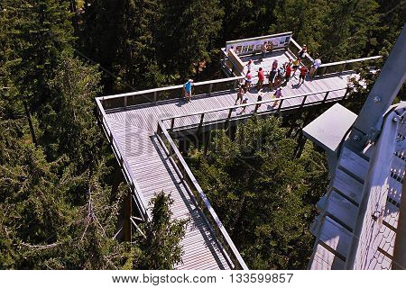 2015-07-04 Lipno nad Vltavou Czech republic - several tourists standing on a wooden footbridge of new tourist attraction 'Stezka korunami stromu' in South Bohemia which has been opened in 10. July 2012