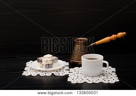 Mug with coffee Cezve and Turkish delight on black background
