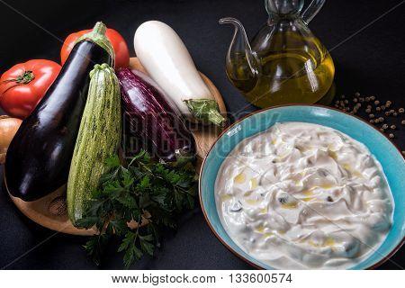 Plate of tzatziki salad with raw eggplants and tomatoes
