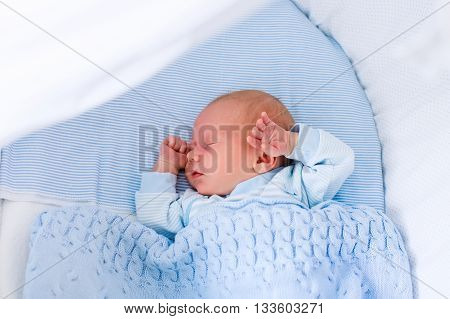 Newborn baby boy in bed. New born child sleeping under a blue knitted blanket. Children sleep. Bedding for kids. Infant napping in bed. Healthy little kid shortly after birth. Cable knit textile.