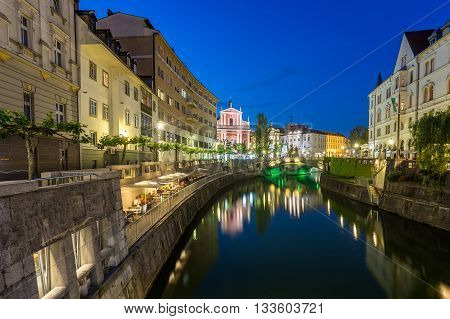 LJUBLJANA SLOVENIA - 26TH MAY 2016: A view along the Ljubljana canal towards the Franciscan Church of the Annunciation and Preseren Square at night. Other buildings and people can be seen.