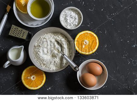 Ingredients for making orange cake with olive oil - flour eggs olive oil powdered sugar on a dark stone background