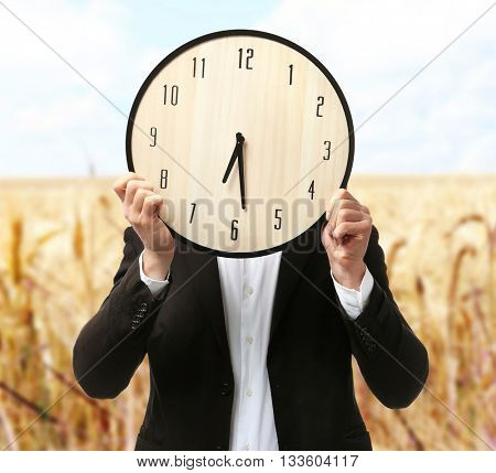 Man in black suit covering his face with big clock on blurred field background