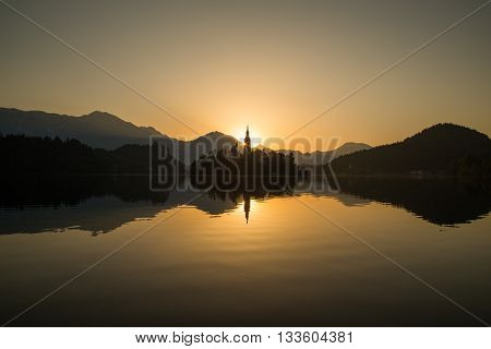 Church of the Assumption on Bled Lake at sunrise. Hills and mountains can be seen the distance.