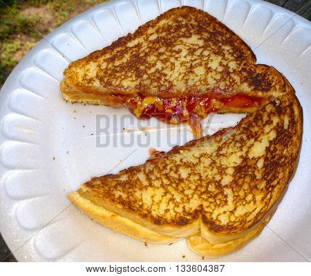 A freshly grilled peanut butter and jelly sandwich outside on a styrafoam plate with focus directed at the jelly and peanut butter