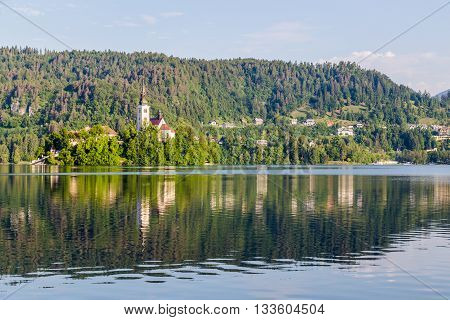 The Church of the Assumption on Bled Lake in the morning. Other buildings can be seen in the distance