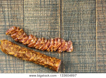 Polish sausage chorizo in the piece and sliced on a wooden background. Horizontal flat top view