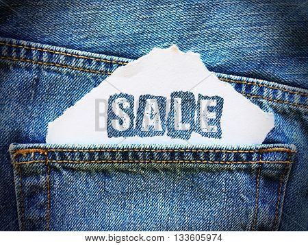 sale word on white paper in the pocket of blue denim jeans