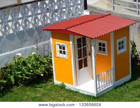 Yellow tiny house on the green in a garden