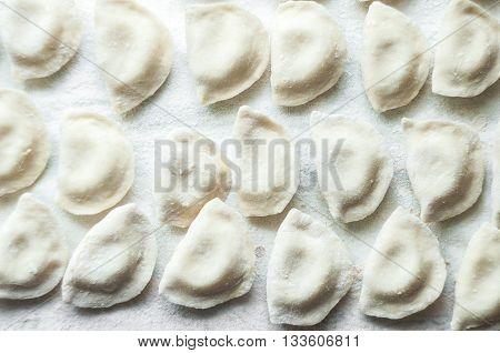 Raw ravioli. A lol of raw raviolis on a tables