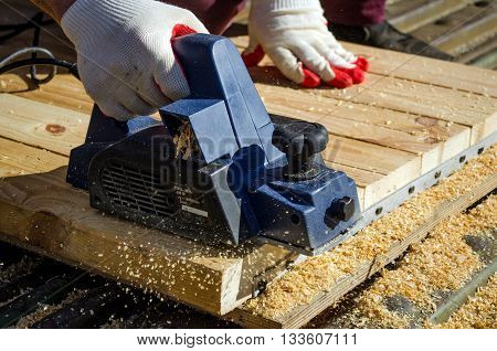 The hand of a man working with an electric planer and planed boards