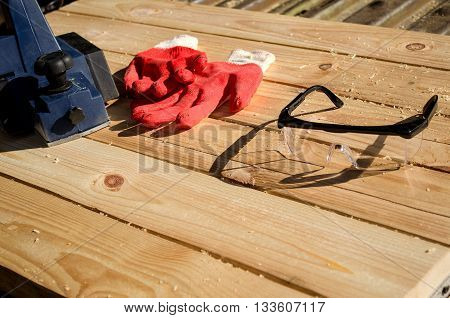 Electric planer gloves and goggles on planed boards
