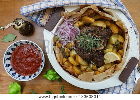 Traditional Greek kleftiko, an oven-baked lamb stew with mizithra cheese, olive oil, onion, carrot, garlic and herbs, served with lemon roast potatoes.