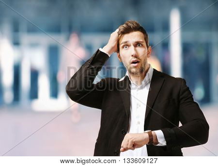 Businessman running late for work on blurred urban background