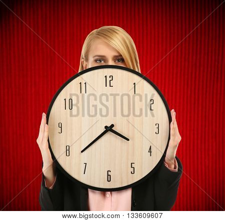 Young attractive woman holds a clock on red background