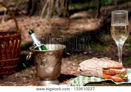 A glass of champagne on a stump in the woods and a champagne bucket with a bottle and sandwiches on the grass