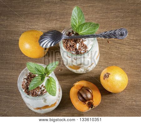 Fresh Yogurt with Loquats and Flaxseed on Rustic Background. Top view.