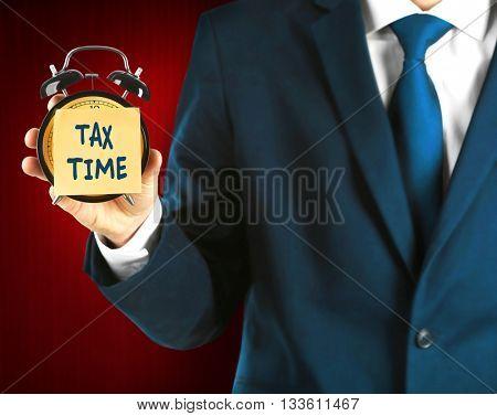 Tax concept. Businessman holding alarm clock on dark red background