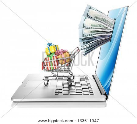 Online shopping concept. Laptop with money from monitor screen and small shopping cart full of gifts isolated on white background