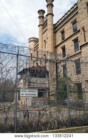 JOLIET, ILLINOIS / UNITED STATES - MAY 3, 2015: A tall chain-link fence, topped with razor wire, deters intruders from trespassing upon the old Illinois State Penitentiary, now vacant and abandoned.