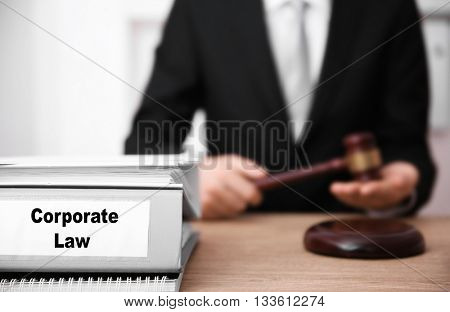 Young female judge working in her office. Folder with label Corporate Law on foreground