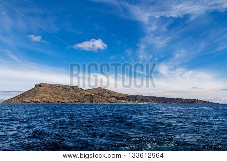 Photograph of the whole Amantani island from the point of view of a boat on the waters of Lake Titicaca Puno Peru. The sky and the water are blue and it is also possible to see clouds in the sky trees and houses on the island and waves in the water.