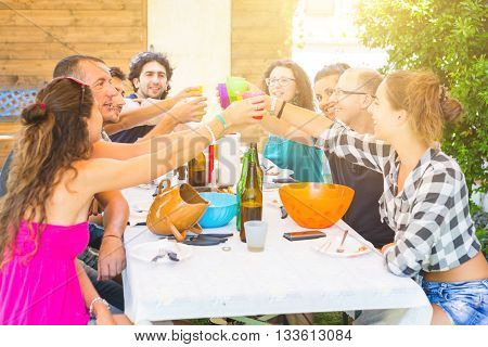 A group of people sitting on the table having lunch. A multicultural group of friends is toasting while they are eating. They are having fun together. Everybody is wearing summer clothes.