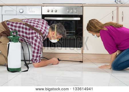 Woman Looking At Male Worker Spraying Insecticide On Wooden Cabinet In Kitchen
