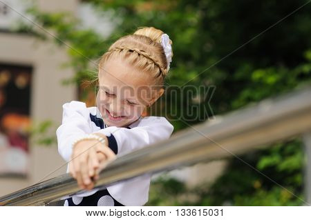 Portrait of a little girl. Child in a beautiful dress looking to side, hands on railing. Green tree in background. little girl laughs