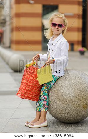 Young little girl with full shopping bags standing near boutique. Pretty smiling girl with shopping bags. Portrait of a kid with shopping bags. Child in sunglasses, near shopping mall having fun.
