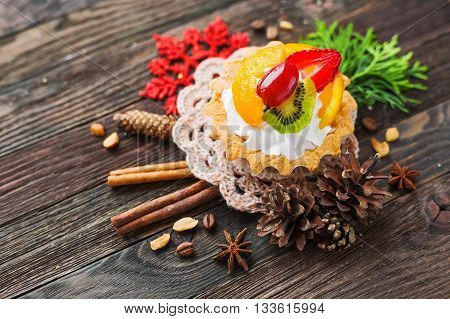 Winter holiday rustic background with fruit tart and spices - cinnamon anise peanuts. Christmas and New Year decorations - red snowflake thuja and pine cones. Tasty dessert with strawberry kiwi orange peach and whipped cream.