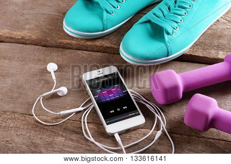 White smart phone with headphones, pink dumb bells and gumshoes on wooden background