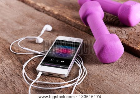 White smart phone with headphones and pink dumb bells on wooden background