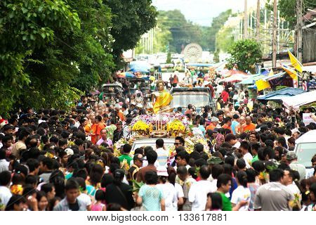 SARABURI,THAILAND -AUGUST 2,2012 : Group of monks receiving flower offering from people and Buddha on parade in Tak Bat Dok Mai or Flower Offering Ceremony at Phrabuddhabat Woramahavihan Temple , Saraburi Province,Thailand.